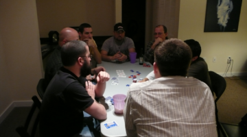 A live no limit holdem game with several players around a table.